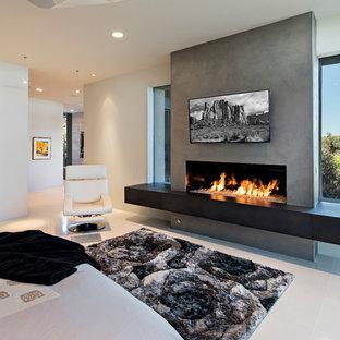 Пример оригинального дизайна: огромная хозяйская спальня в современном стиле с полом из известняка, горизонтальным камином, белым полом, разноцветными стенами и фасадом камина из штукатурки