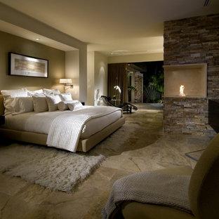 Idee per una grande camera matrimoniale design con pareti beige, pavimento in travertino, camino ad angolo e cornice del camino in pietra