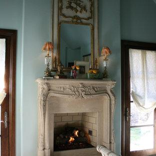 Inredning av ett medelhavsstil litet gästrum, med mörkt trägolv, en standard öppen spis, en spiselkrans i sten och blå väggar