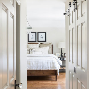 Idéer för ett mellanstort klassiskt huvudsovrum, med mellanmörkt trägolv och beige väggar