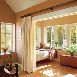 Inredning av ett klassiskt mellanstort gästrum, med orange väggar och mellanmörkt trägolv