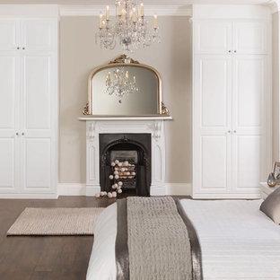 Стильный дизайн: хозяйская спальня среднего размера в стиле современная классика с белыми стенами, темным паркетным полом, стандартным камином и фасадом камина из металла - последний тренд