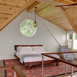 Design ideas for a beach style loft-style bedroom in Cleveland with white walls and medium hardwood floors.