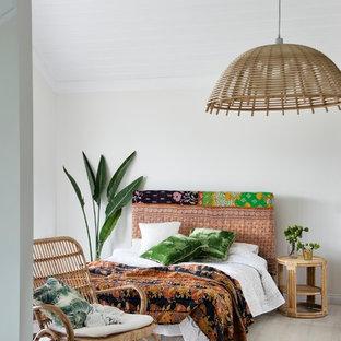 Imagen de habitación de invitados exótica, sin chimenea, con paredes blancas y suelo de madera clara