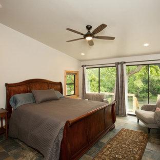 Ejemplo de dormitorio rural, de tamaño medio, con paredes blancas, suelo de pizarra y suelo multicolor