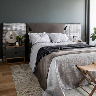 Design ideas for a beach style master bedroom in Other with grey walls, medium hardwood floors and brown floor.
