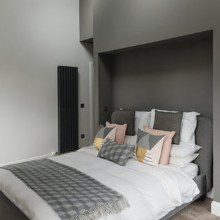 Contemporary bedroom in Glasgow with white walls and brown floors.