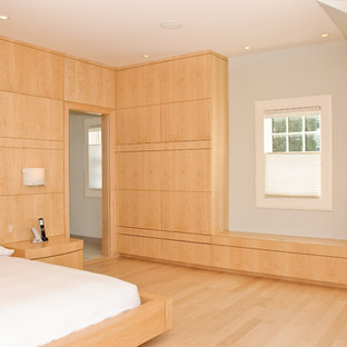 Design ideas for a modern bedroom in Portland Maine with white walls, light hardwood floors and no fireplace.