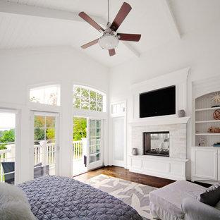Diseño de dormitorio principal, costero, grande, con paredes blancas, suelo de madera oscura, marco de chimenea de piedra y chimenea de doble cara