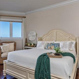Coastal dark wood floor bedroom photo in Miami with beige walls
