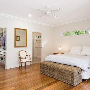 This is an example of a country master bedroom in Brisbane with grey walls, medium hardwood floors and brown floor.