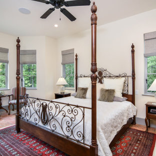 This is an example of a mid-sized mediterranean master bedroom in Other with white walls, terra-cotta floors, no fireplace and multi-coloured floor.