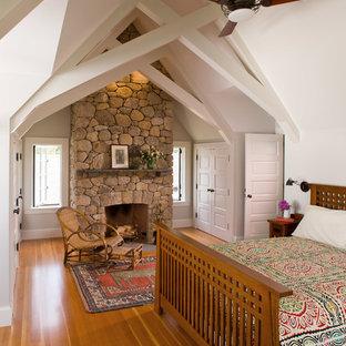 Immagine di una camera matrimoniale costiera con pareti bianche, pavimento in legno massello medio, camino classico e cornice del camino in pietra