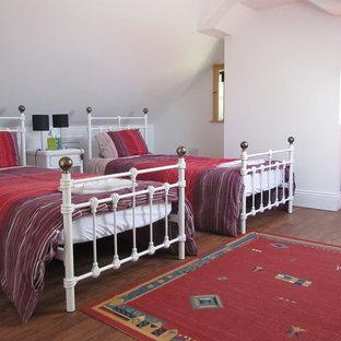 Immagine di una camera degli ospiti country di medie dimensioni con pareti rosa, pavimento in bambù e nessun camino