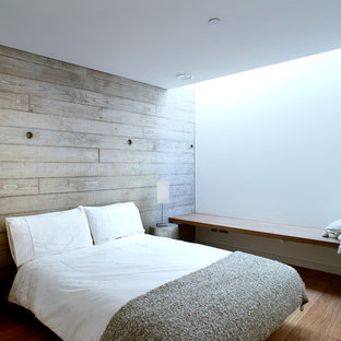 Example of a mid-sized minimalist guest medium tone wood floor bedroom design in Hampshire with white walls and no fireplace