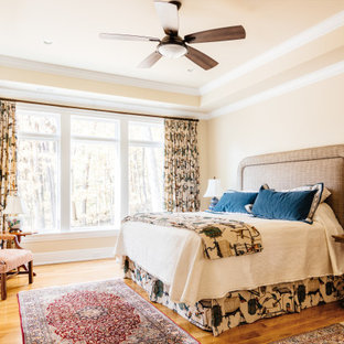 Example of a large transitional master medium tone wood floor, brown floor and tray ceiling bedroom design in Nashville with beige walls