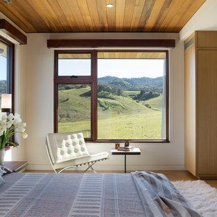 Modern inredning av ett stort sovrum, med vita väggar, ljust trägolv och beiget golv
