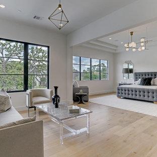 ヒューストンの広い地中海スタイルのおしゃれな主寝室 (白い壁、淡色無垢フローリング、ベージュの床)