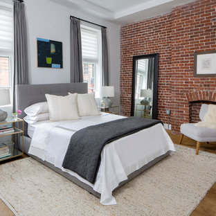 Стильный дизайн: хозяйская спальня в стиле современная классика с серыми стенами, светлым паркетным полом, стандартным камином и фасадом камина из кирпича - последний тренд