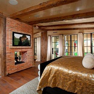 Diseño de dormitorio principal, mediterráneo, con paredes beige, suelo de madera oscura, chimenea de doble cara y marco de chimenea de ladrillo