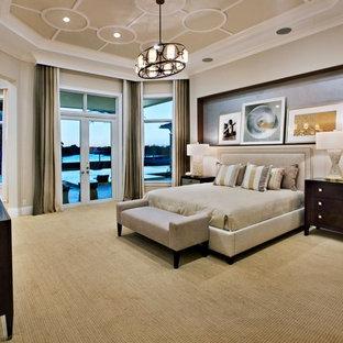 Foto di una grande camera matrimoniale tropicale con pareti beige, moquette e nessun camino