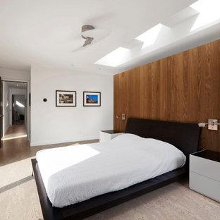 Modelo de dormitorio principal, moderno, de tamaño medio, con paredes blancas, suelo de corcho y suelo beige