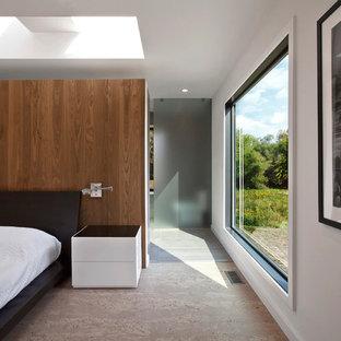 На фото: хозяйская спальня среднего размера в стиле модернизм с белыми стенами, пробковым полом и бежевым полом