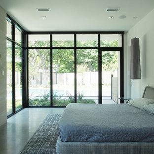 Diseño de dormitorio principal, moderno, de tamaño medio, con paredes beige, suelo de piedra caliza, chimenea lineal, marco de chimenea de piedra y suelo marrón