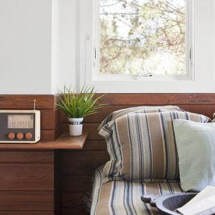 Idee per una piccola camera degli ospiti minimal con pareti bianche, pavimento in legno massello medio e pavimento marrone