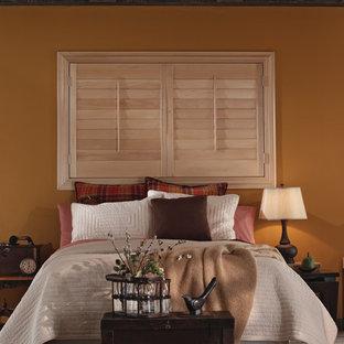 Modelo de habitación de invitados tradicional renovada, de tamaño medio, con paredes amarillas y suelo de madera en tonos medios