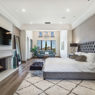 Inspiration for a huge mediterranean master dark wood floor and brown floor bedroom remodel in San Francisco with gray walls and a standard fireplace