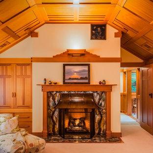 Esempio di una camera matrimoniale american style di medie dimensioni con pareti beige, moquette, camino classico, cornice del camino piastrellata e pavimento beige