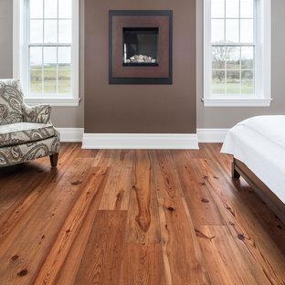 Imagen de dormitorio principal, de estilo de casa de campo, grande, con paredes grises, suelo de madera en tonos medios, chimeneas suspendidas, marco de chimenea de yeso y suelo marrón