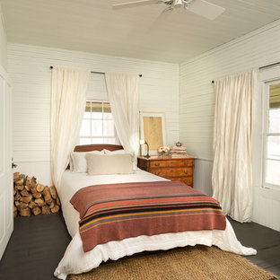 This is an example of a small country bedroom in Atlanta with white walls, painted wood floors and black floor.