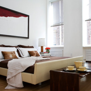 Example of a huge trendy master brown floor and light wood floor bedroom design in New York with white walls and no fireplace