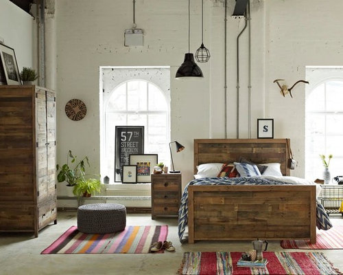 this is an example of a medium sized industrial bedroom in surrey with white walls and