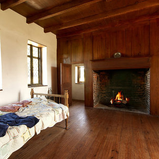 Photo of a mid-sized traditional guest bedroom in New York with white walls, dark hardwood floors, a standard fireplace and a wood fireplace surround.
