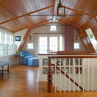 Ejemplo de dormitorio tipo loft, rural, grande, con paredes beige, suelo de madera en tonos medios, chimenea tradicional, marco de chimenea de ladrillo y suelo marrón