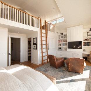 Ejemplo de dormitorio tipo loft, costero, grande, con paredes blancas, suelo de madera clara y suelo beige