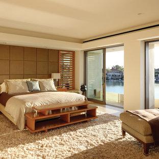 Cette image montre une grand chambre parentale design avec un mur noir, un sol marron, un sol en travertin et aucune cheminée.