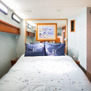 Стильный дизайн: маленькая хозяйская спальня с синими стенами, паркетным полом среднего тона и оранжевым полом - последний тренд