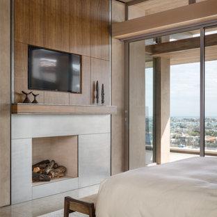 На фото: большая хозяйская спальня в современном стиле с коричневыми стенами, полом из керамогранита, стандартным камином и фасадом камина из плитки