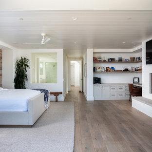 Modelo de dormitorio principal, costero, de tamaño medio, con paredes blancas, suelo de madera en tonos medios, chimenea tradicional y marco de chimenea de ladrillo