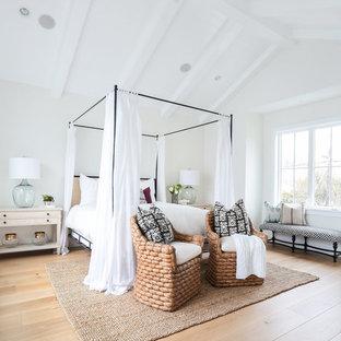 Ejemplo de dormitorio principal, costero, con paredes blancas y suelo de madera clara