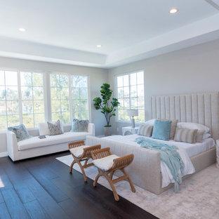 Großes Modernes Hauptschlafzimmer mit beiger Wandfarbe, dunklem Holzboden, braunem Boden, Kamin und Kaminumrandung aus Holz in Sonstige