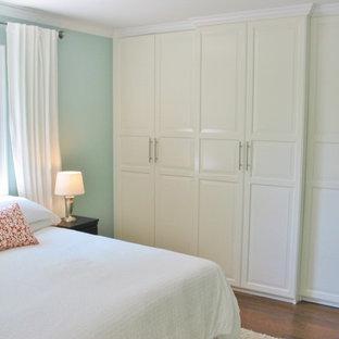 Elegant master medium tone wood floor bedroom photo in Cincinnati with blue walls