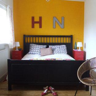 Idées déco pour une chambre éclectique avec un mur jaune, un sol en bois brun et aucune cheminée.