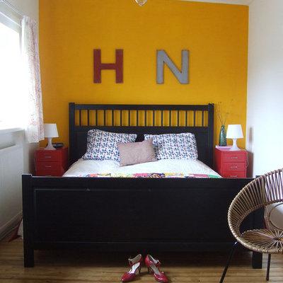 Bedroom - eclectic medium tone wood floor bedroom idea in Amsterdam with yellow walls and no fireplace