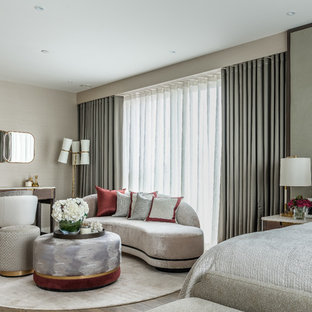 Large contemporary master bedroom in London with no fireplace, beige walls and dark hardwood flooring.