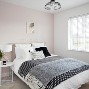 This is an example of a scandinavian bedroom in Other with pink walls, carpet, no fireplace and grey floors.